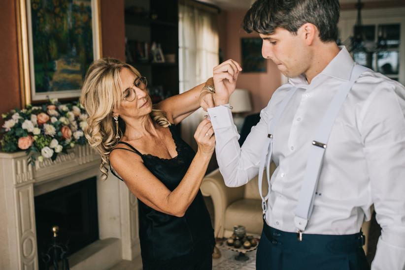madre dello sposo che aiuta lo sposo ad allacciarsi i polsini della camicia