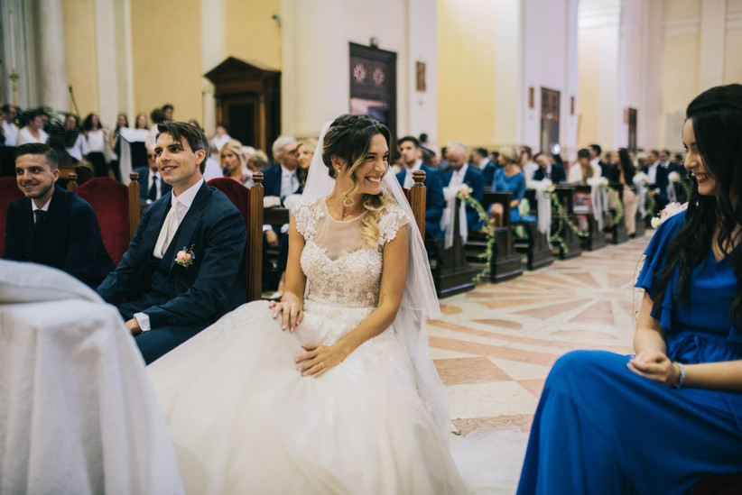 sposa che guarda un'amica durante cerimonia religiosa