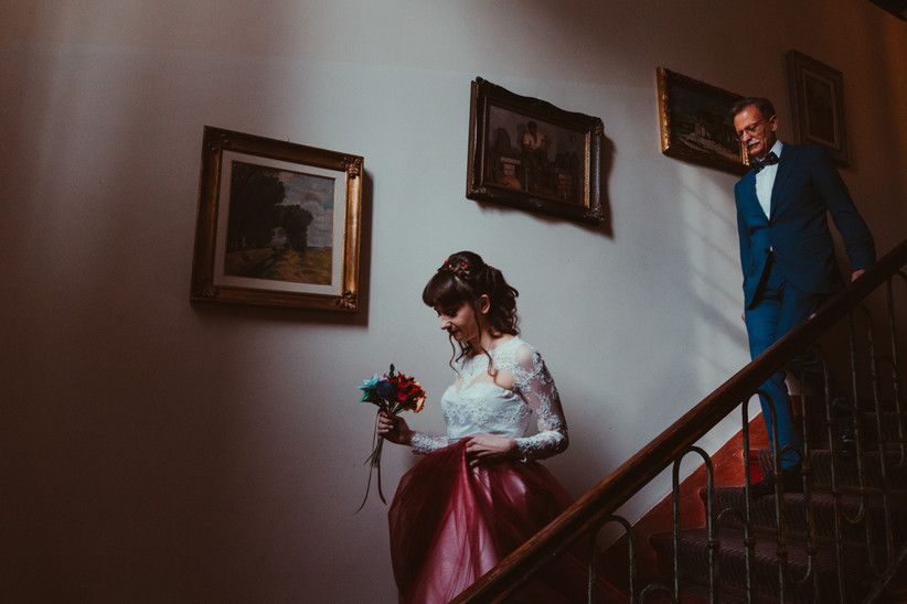 sposa e papà della sposa che scendono le scale di casa