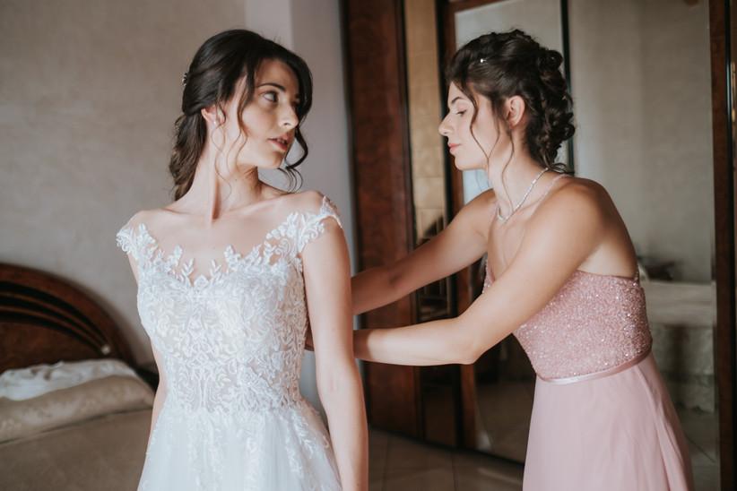 invitata che allaccia il vestito alla sposa