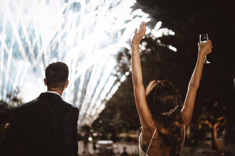 sposi di spalle che guardano i fuochi d'artificio