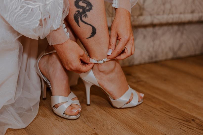 dettaglio sposa che si allaccia il cinturino delle scarpe
