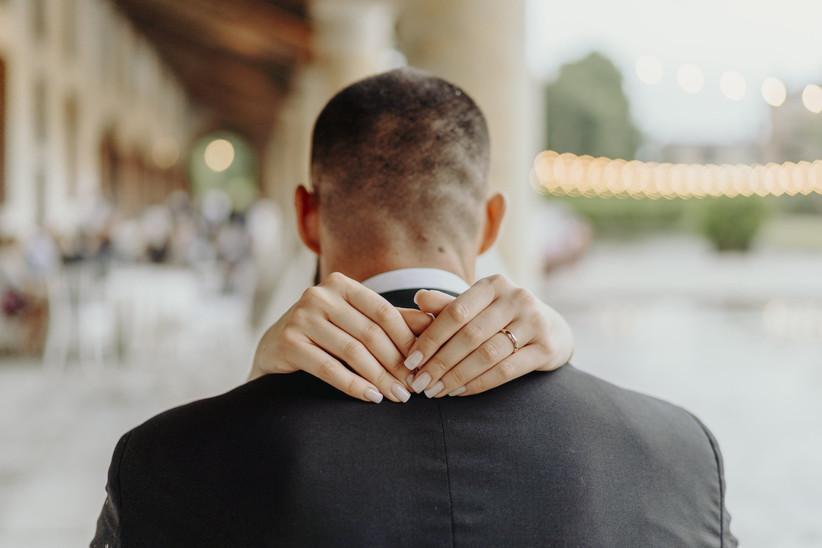sposi che si abbracciano, dettaglio su anello matrimonio