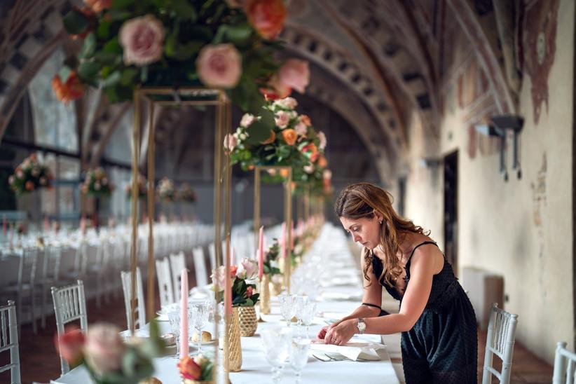 wedding planner che allestisce tavolo nuziale
