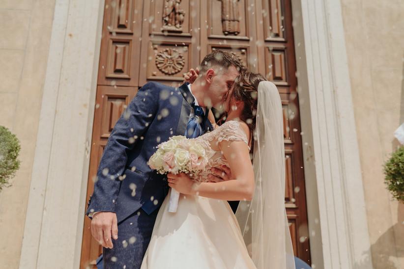 sposi che si baciano fuori dalla chiesa durante lancio del riso