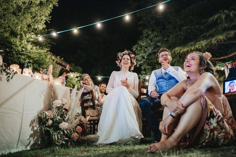 sposi che ridono davanti a una videoproiezioni durante il ricevimento