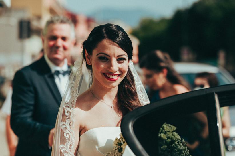 sposa che esce dall'auto e sorride alla fotocamera