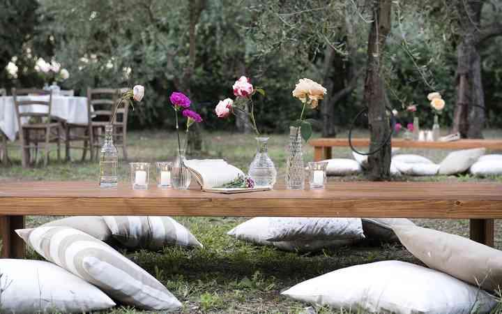 allestimento tavolo basso con cuscini in giardino