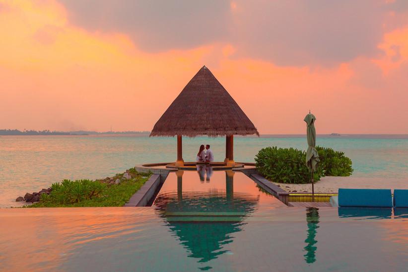 sposi in viaggio di nozze in resort con piscina vista mare al tramonto