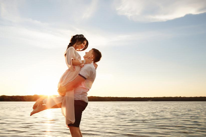 Sposo con in braccio sposa sul mare al tramonto