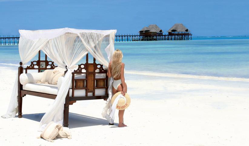 spiaggia maldiviana con palafitte e ragazza che guarda il mare
