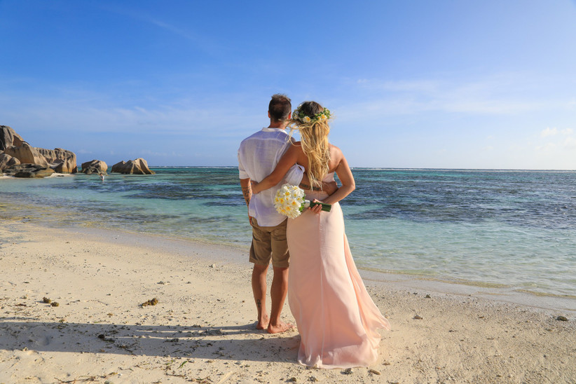 Sposi su una spiaggia mentre guardano il mare