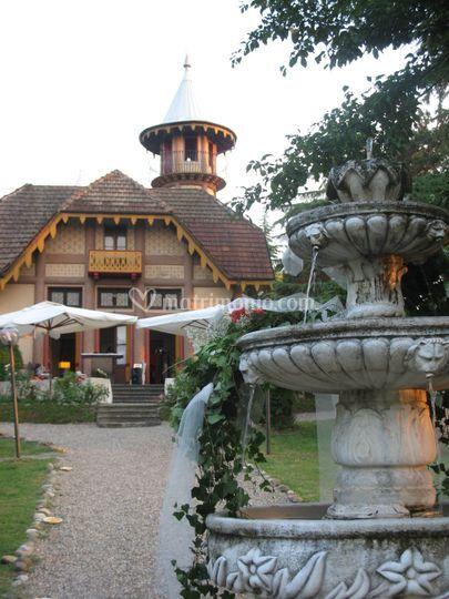 Villa crocioni - fontana con fiori e sul fondo facciata villa