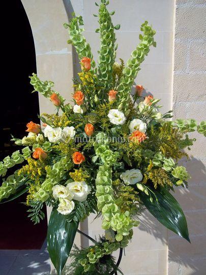 Composizione con rose arancio, molucella, lisianthus bianco, soldigago e aspidistria
