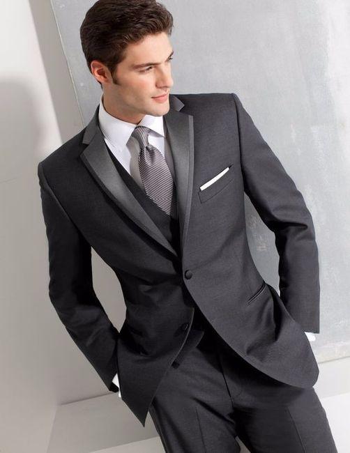 A) Con un elegante vestito grigio